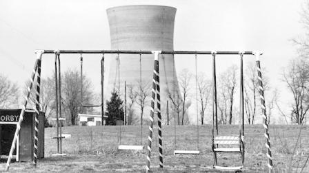 FILE - This file photo from March 30, 1979 shows a cooling tower of the Three Mile Island nuclear power plant near Harrisburg, Pa., as it looms behind an abandoned playground. The partial meltdown at Three Mile Island nuclear plant in 1979 routed more than 180,000 people living within 50 miles of t