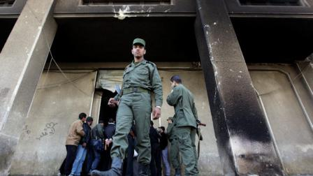 A Syrian army soldier steps out from the burned court building that was set on fire by Syrian anti-government protesters, in the southern city of Daraa, Syria, on Monday March 21, 2011. Mourners chanting No more fear! have marched through a Syrian city where anti-government protesters had deadly confrontations with security forces in recent days. The violence in Daraa, a city of about 300,000 near the border with Jordan, was fast becoming a major challenge for President Bashar Assad, who tried to contain the situation by freeing detainees and promising to fire officials responsible for the violence. (AP Photo/Hussein Malla)