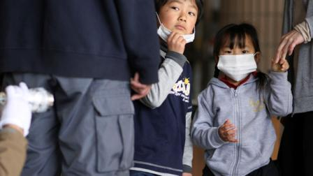Children watch their father is screened for radiation at a shelter, Tuesday, March 29, 2011, in Fukushima, Fukushima prefecture, Japan. Highly toxic plutonium is seeping from the damaged nuclear power plant in Japans tsunami disaster zone into the soil outside, officials said Tuesday, further complicating the delicate operation to stabilize the overheated facility.
