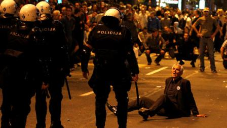 A men sits on the ground as members of the riot police approach him after a rally organized by the ultranationalist Serbian Radical Party in front of the Parliament building, in Belgrade, Serbia, on Sunday, May 29, 2011. Mladic was arrested on Thursday in a village in Serbia after 16 years on the run.