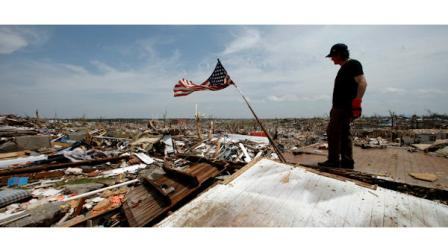 Brent Long looks over a devastated Joplin, Mo. neighborhood as he helps a friend salvage belongings Monday, May 30, 2011. An EF-5 tornado tore through much of the city May 22, damaging a hospital and hundreds of homes and businesses and killing at least 139 people. (AP Photo/Charlie Riedel)