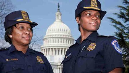 Officers Yogananda Yogi Pittman, left, and Monique Moore, right, the first two African-American women to be promoted to the rank of captain on the U.S. Capitol Police force, stand together on the East Lawn of the Capitol in Washington, Monday, March 19, 2012. (AP Photo/J. Scott Applewhite)