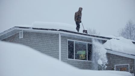 14-year-old Doug Hamrick shovels snow off of his familys roof Thursday, Jan.12, 2012, in Anchorage. (AP Photo/Loren Holmes)