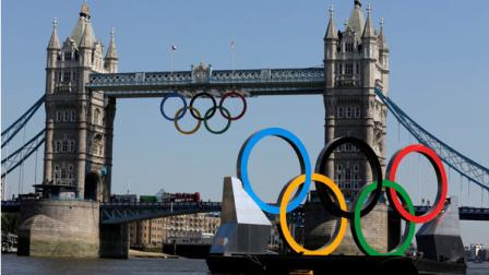 Olympic Rings hang from the Tower Bridge beyond a set of rings floating on the River Thames Thursday, July 26, 2012, in London.