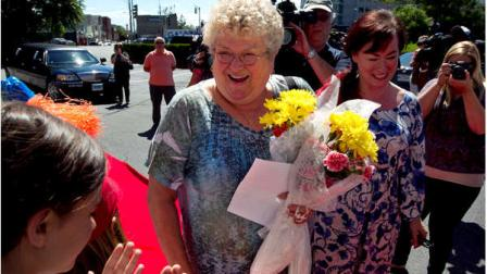 Bus monitor Karen Klein, of Greece, N.Y., holds flowers as she is welcomed to an award ceremony in her honor at a radio station, in Boston on Thursday, June 28, 2012. A viral video of Klein being bullied by four middle schoolers shows the 68-year-old school bus monitor trying her best to ignore the stream of profanity, insults and outright threats directed at her aboard a bus in New York state. (AP Photo/Steven Senne)