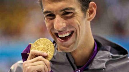 United States Michael Phelps displays his gold medal for the mens 100-meter butterfly swimming final at the Aquatics Centre in the Olympic Park during the 2012 Summer Olympics in London, Friday, Aug. 3, 2012. (AP Photo/Matt Slocum)