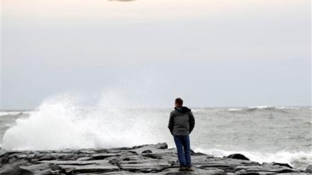 Resident Brian Dougherty looks at the waves from the beach in Ocean City, Md., as Hurricane Sandy approaches the Atlantic Coast, on Saturday, Oct. 27, 2012. ( AP Photo/Jose Luis Magana)