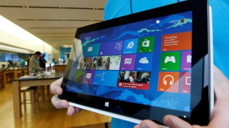 A Microsoft store product advisor displays the new Surface table computer as customers enter the store as it opens Friday, Oct. 26, 2012 in Seattle. (AP Photo/Elaine Thompson)