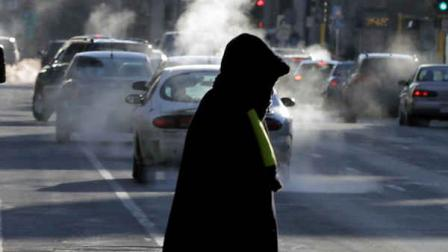 Steam from cars exhaust rises as a woman dressed for the weather crosses a street Tuesday, Jan. 22, 2013 in downtown Minneapolis where temperatures were in the double-digit, sub-zero numbers. (AP Photo/Jim Mone)