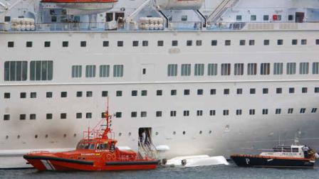 An orange rescue boat docks by a capsized lifeboat from the British-operated cruiseship Thomson Majesty in Santa Cruz port of the Canary Island of La Palma, Spain, Sunday Feb. 10, 2013.  (AP Photo/Manuel Gonzalez)