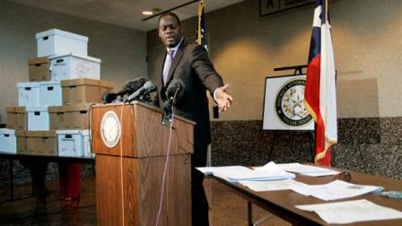 Dallas County District Attorney Craig Watkins addresses members of the media as he presents some historical documents and other memorabilia, in boxes to left and on table to right, connected to the assassination of President John F. Kennedy during a press conference in Dallas, Monday, Feb. 18, 2008. (AP Photo/Tony Gutierrez)