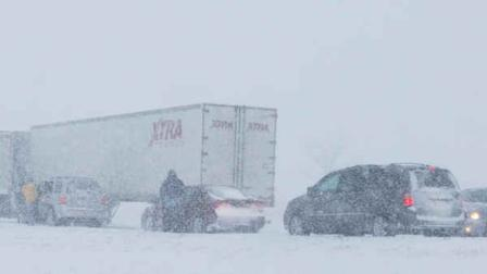 Drivers get out of their vehicles after a ramp is blocked by truck stuck in snow along I-35 in the Kansas City suburb of Overland Park.  (AP Photo/Orlin Wagner)