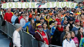 A crowd gathers at the finish line of the Boston Marathon in Boston for a Sports Illustrated photo shoot to commemorate the one-year anniversary of the Boston Marathon bombings, Saturday, April 12, 2014. (AP Photo/Michael Dwyer)