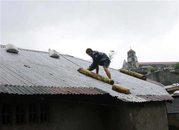 "<div class=""meta ""><span class=""caption-text "">A man reinforces his house with banana stalks as powerful typhoon Haiyan hits Legazpi city, Albay province about 520 kilometers ( 325 miles) south of Manila, Philippines Friday. Typhoon Haiyan,  one of the most powerful typhoons ever recorded slammed into the Philippines on Friday, setting off landslides, knocking out power in one entire province and cutting communications in the country's central region of island provinces. (AP Photo/Nelson Salting)</span></div>"