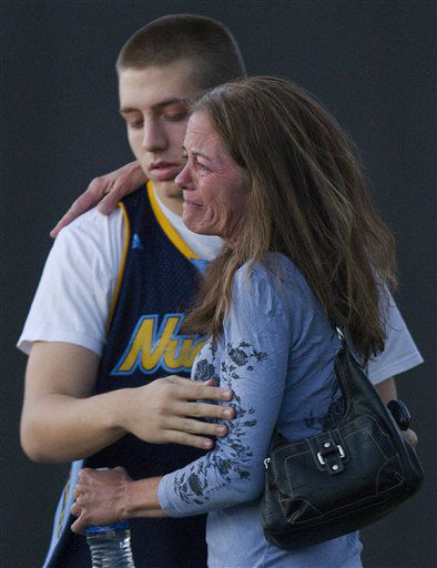Jacob Stevens, 18, hugs his mother Tammi Stevens after being interview by police outside Gateway High School where witness were brought for questioning after a shooting at a movie theater, Friday, July 20, 2012 in Denver. A gunman wearing a gas mask set off an unknown gas and fired into a crowded movie theater at a midnight opening of the Batman movie &#34;The Dark Knight Rises&#34;. &#40;AP Photo&#47;Barry Gutierrez&#41; <span class=meta>(AP Photo&#47; Barry Gutierrez)</span>