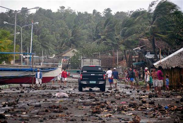 "<div class=""meta ""><span class=""caption-text "">Debris litter the road by the coastal village in Legazpi city following a storm surge brought about by powerful Typhoon Haiyan in Albay province Friday, Nov. 8, 2013, about 520 kilometers ( 325 miles) south of Manila, Philippines. The strongest typhoon this year slammed into the central Philippines on Friday, setting off landslides and knocking out power and communication lines in several provinces. (AP Photo/Nelson Salting)</span></div>"