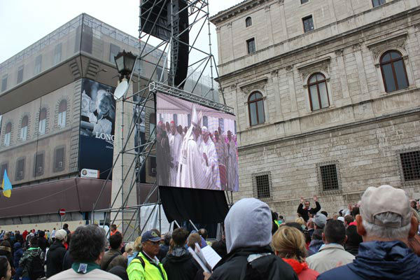 The crowd watches on a video screen as Pope Francis and Pope Benedict greet each other. <span class=meta>(Photo&#47;John Morris)</span>
