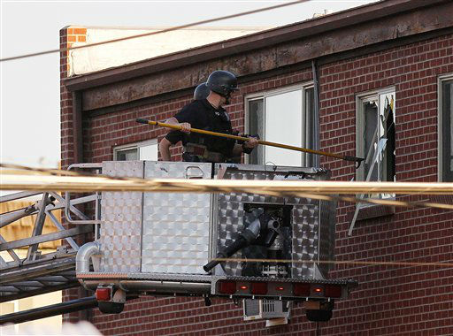 "<div class=""meta ""><span class=""caption-text "">Police break out a window of an apartment  where the suspect in a shooting at a movie theatre lived in Aurora, Colo., Friday, July 20, 2012. (AP Photo/ Ed Andrieski)</span></div>"