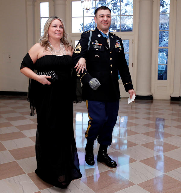 Medal of Honor recipient Sgt. 1st Class Leroy Petry and his wife Ashley Petry arrive at the Booksellers area of the White House in Washington for the State Dinner hosted by President Barack Obama and first lady Michelle Obama for British Prime Minister David Cameron and his wife Samantha, Wednesday, March 14, 2012. (AP Photo/Charles Dharapak)