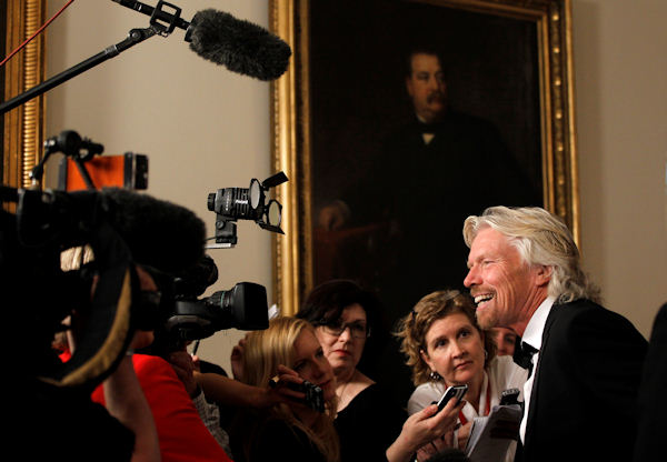 Sir Richard Branson talks to reporters as he arrives at the Booksellers area of the White House in Washington for the State Dinner hosted by President Barack Obama and first lady Michelle Obama for British Prime Minister David Cameron and his wife Samantha, Wednesday, March 14, 2012. (AP Photo/Charles Dharapak)
