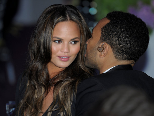 Chrissy Teigen, left, a model well-known for her swimsuit photos talks with her boyfriend and singer John Legend, right, during a State Dinner at the White House in Washington, Wednesday, March 14, 2012. (AP Photo/Susan Walsh)