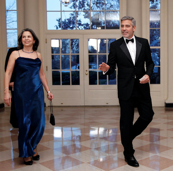 Actor George Clooney arrives at the Booksellers area of the White House in Washington for the State Dinner hosted by President Barack Obama and first lady Michelle Obama for British Prime Minister David Cameron and his wife Samantha, Wednesday, March 14, 2012. At left is Maria Otero, Undersecretary for Civilian Security, Democracy and Human Rights. (AP Photo/Charles Dharapak)