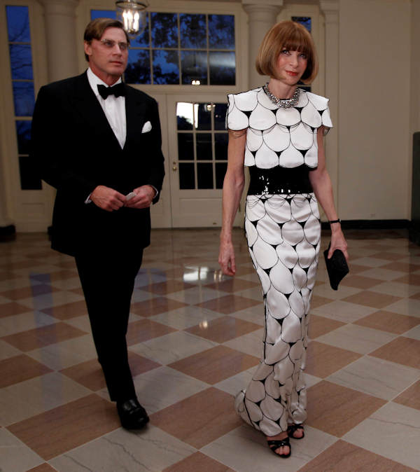 Anna Wintour, Editor-in-Chief of Vogue Magazine, walks with Shelby Bryan as they arrive at the Booksellers area of the White House in Washington for the State Dinner hosted by President Barack Obama and first lady Michelle Obama for British Prime Minister David Cameron and his wife Samantha, Wednesday, March 14, 2012. (AP Photo/Charles Dharapak)