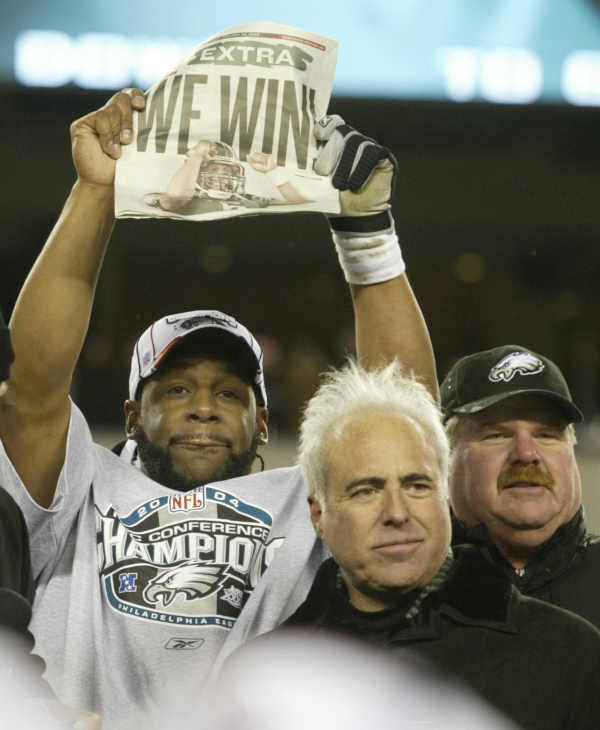 Philadelphia Eagles quarterback Donovan McNabb stands next to Eagles owner Jeffrey Lurie, center, and head coach Andy Reid as he holds a paper declaring the Eagles victory over the Atlanta Falcons in the NFC Championship games in Philadelphia Sunday Jan. 23, 2005. The Eagles defeated the Falcons 27-10. (AP Photo/Rusty Kennedy)