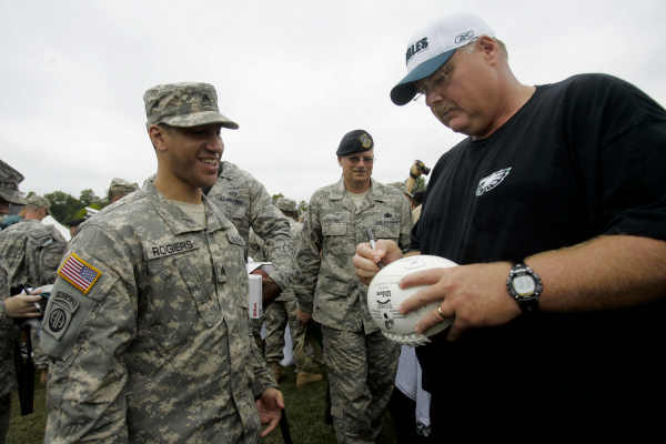 Philadelphia Eagles head coach Andy Reid signs autographs for members of the United States military after the Eagles morning session of NFL football training camp at Lehigh University in Bethlehem, Pa. on Tuesday, Aug. 3, 2010. The team held its annual Military Day with over 300 members of all four branches of the armed forces in attendance. (AP Photo/Rich Schultz)