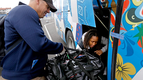 United States women's bobsled head coach Todd Hays, left, helps brakeman Lauryn Williams, who was born in Rochester, Pennsylvania, load luggage into a waiting bus as the team arrives for the 2014 Winter Olympics, Thursday, Jan. 30, 2014, in Sochi, Russia. (AP Photo/David Goldman, Pool)