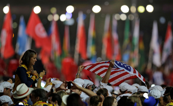An athlete holds the U.S. flag as he enters the stadium with others during the Closing Ceremony at the 2012 Summer Olympics, Sunday, Aug. 12, 2012, in London. (AP Photo/Matt Slocum)