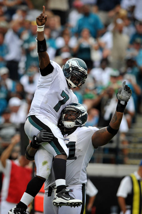 Philadelphia Eagles quarterback Michael Vick (7) is lifted in the air by teammate Philadelphia Eagles offensive tackle Jason Peters (71) after throwing a touchdown pass in the second quarter during an NFL football game against the Jacksonville Jaguars in Jacksonville, Fla., Sunday, Sept. 26, 2010. (AP Photo/Stephen Morton)