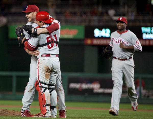 Philadelphia Phillies first baseman Ryan Howard, right, runs to celebrate with pitcher Roy Halladay, left, and catcher Carlos Ruiz after the Phillies defeated the Washington Nationals 8-0 to clinch the National League East on Monday, Sept. 27, 2010, in Washington. <span class=meta>(AP Photo&#47;Evan Vucci)</span>
