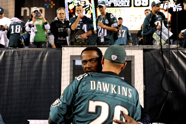 Former Philadelphia Eagles safety Brian Dawkins, back, is hugged by a person wearing his jersey before an NFL football game between the Philadelphia Eagles and the New York Giants Sunday, Sept. 30, 2012, in Philadelphia. The Eagles retired Dawkins number during the a pre-game news conference. (AP Photo/Michael Perez)