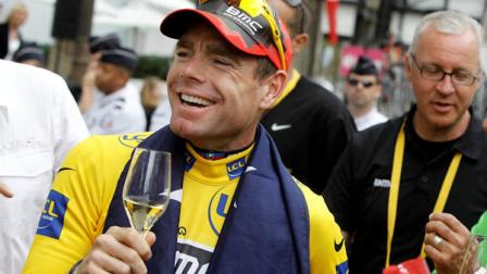 Tour de France winner Cadel Evans of Australia, wearing the overall leaders yellow jersey, is given a glass of wine on the Champs Elysees during the victory parade after winning the Tour de France cycling race in Paris, France, Sunday July 24, 2011. (AP Photo/Laurent Cipriani)