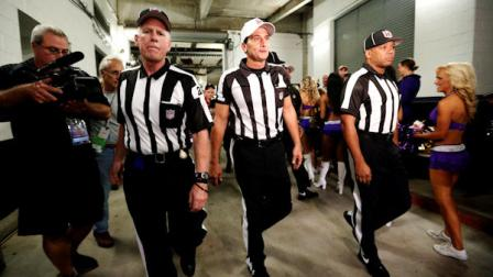 Officials walk toward the field before an NFL football game between the Baltimore Ravens and Cleveland Browns in Baltimore, Thursday, Sept. 27, 2012. (AP Photo/Patrick Semansky)