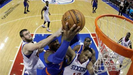 New York Knicks Carmelo Anthony, center, battles for a rebound with Philadelphia 76ers Spencer Hawes, left, and Evan Turner during the first half of an NBA basketball game, Saturday, Jan. 26, 2013, in Philadelphia. (AP Photo/Matt Slocum)