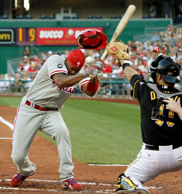 Philadelphia Phillies Jimmy Rollins, left loses his helmet after being hit by a pitch as Pittsburgh Pirates catcher Ryan Doumit reaches for the pitch by Ross Ohlendorf in the third inning of the baseball game in Pittsburgh, Friday, July 2, 2010. (AP Photo/Keith Srakocic)
