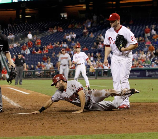 Arizona Diamondbacks' Adam Eaton scores as Philadelphia Phillies' pitcher Casper Wells watches in the eighteenth inning of an MLB National League baseball game Saturday, Aug. 24, 2013, in Philadelphia. The Diamondbacks won 12-7. (AP Photo/H. Rumph Jr)