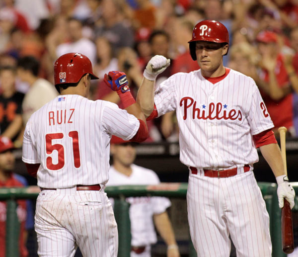 Philadelphia Phillies' Carlos Ruiz (51) celebrates with Cody Asche after hitting a solo home run against the Arizona Diamondbacks in the fifth inning of a baseball game Saturday, Aug. 24, 2013, in Philadelphia. (AP Photo/H. Rumph Jr)