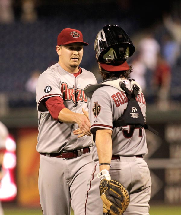 Arizona Diamondbacks pitcher Trevor Cahill, left celebrates with catcher Wil Nieves after Philadelphia Phillies Darin Ruf lined out in the eighteenth inning of a baseball game Sunday, Aug. 25, 2013, in Philadelphia. The Diamond backs won 12-7.(AP Photo/H. Rumph Jr)