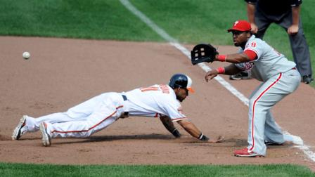 Baltimore Orioles Robert Andino (11) dives back to first safely on a pick-off attempt during the seventh inning of a baseball game against Philadelphia Phillies first baseman Hector Luna (29), Sunday, June 10, 2012, in Baltimore. The Orioles won 5-4 in 10 innings. (AP Photo/Nick Wass)
