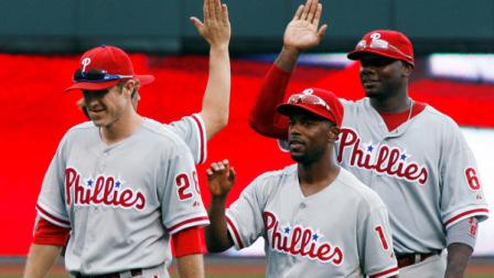 Philadelphia Phillies shortstop Jimmy Rollins (11), third baseman Kevin Frandsen (28) and first baseman Ryan Howard (6) celebrate after defeating the Cincinnati Reds 4-2 in a baseball game, Monday, Sept. 3, 2012, in Cincinnati. (AP Photo/David Kohl)