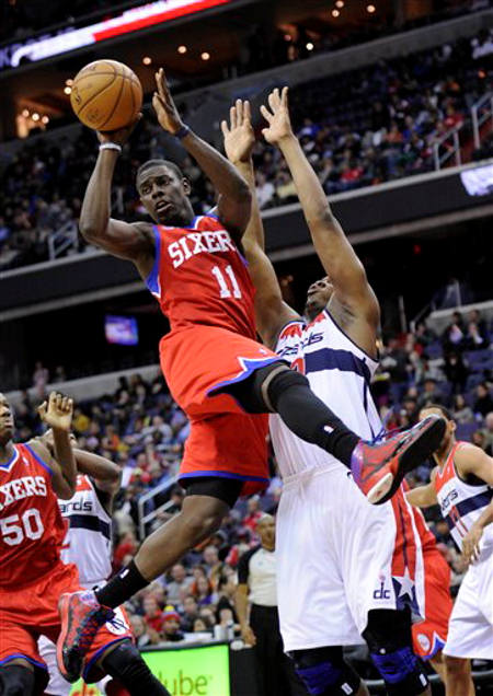 Philadelphia 76ers point guard Jrue Holiday (11) looks to pass against Washington Wizards forward Kevin Seraphin, right, of France, during the first half of an NBA basketball game on Sunday, March 3, 2013, in Washington. (AP Photo/Nick Wass)