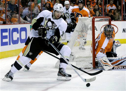 Philadelphia Flyers goalie Ilya Bryzgalov, of Russia (30) watches as Pittsburgh Penguins' James Neal (18) tries to control the puck during the first period of an NHL hockey game Saturday, Jan.19, 2013, in Philadelphia. (AP Photo/Mel Evans)