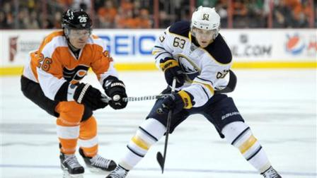 Buffalo Sabres Tyler Ennis (63) bring the puck past Philadelphia Flyers Ruslan Fedotenko (26), of Ukraine, in the first period of an NHL hockey game, Sunday, March 10, 2013, in Philadelphia. (AP Photo/Michael Perez)