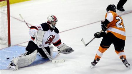 Philadelphia Flyers Claude Giroux, right, scores a goal past New Jersey Devils Johan Hedberg, of Sweden, during a shootout of an NHL hockey game, Friday, March 15, 2013, in Philadelphia. Philadelphia won 2-1 in a shootout. (AP Photo/Matt Slocum)