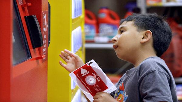 In this photo made Tuesday, June 9, 2009, Sydney Ragpala, 7, waits for a DVD to pop out of a Redbox rental unit in a north Seattle grocery store.  (AP Photo/Elaine Thompson)