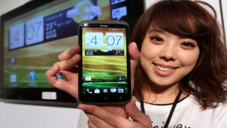 A model displays HTC One X during a press conference in Taipei, Taiwan, Sunday, March 26, 2012. HTC Corp. is marketing the new smartphone that can take four digital photos per second, a model the Taiwan maker hopes can help reverse its falling revenue amid keener competition.