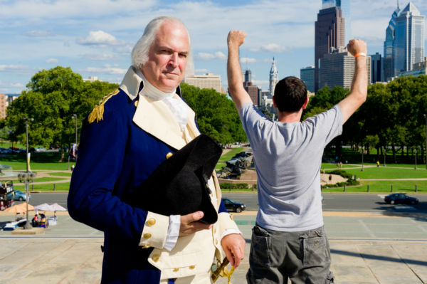 George Washington climbs the steps of the Philadelphia Museum of Art and watches in amusement as tourists recreate the iconic scene